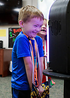 NWA Democrat-Gazette/CHARLIE KAIJO Ace Hughes, 5, of Bella Vista laughs during a magic show, Thursday, July 5, 2018 at the Bella Vista Public Library in Bella Vista. <br /><br />Tommy Terrific performed a musical magic show for youth.