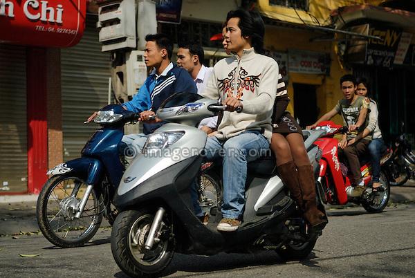 Asia, Vietnam, Hanoi. Hanoi old quarter. Young vietnamese people riding on motorbike through Hanoi.