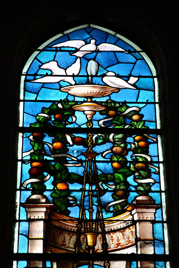 A particular of one of the ancient stained glass windows in the Saint Gervais church in Paris, with doves and oranges. Digitally Improved Photo.