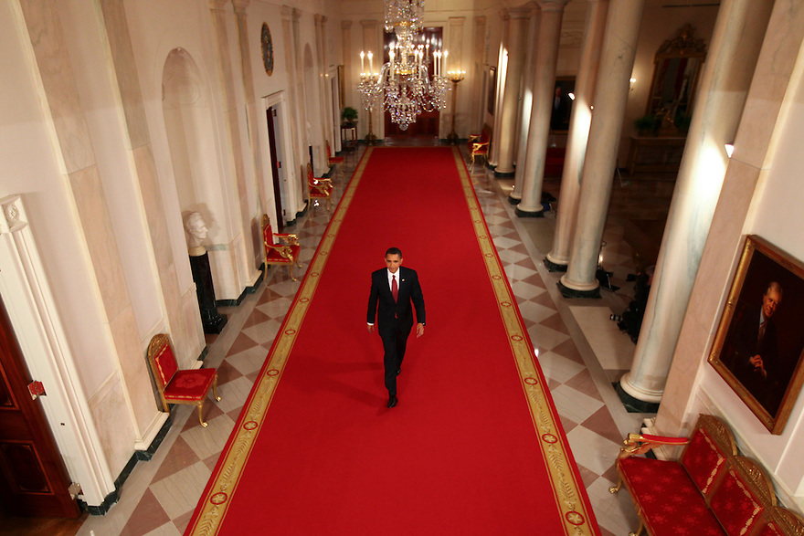 President Barack Obama walks down the Cross Hall towards a news conference in the East Room of the White House in Washington, DC...Photo by Brooks Kraft/Corbis......................