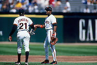 SAN FRANCISCO, CA - Barry Bonds of the San Francisco Giants hands a glove to teammate Deion Sanders during a game at Candlestick Park in San Francisco, California in 1995. Photo by Brad Mangin