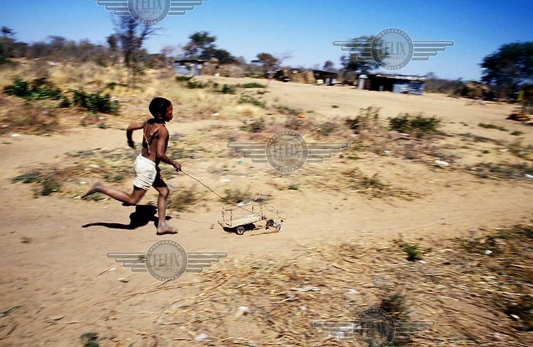 A San boy plays with a toy car made from wire and wood.