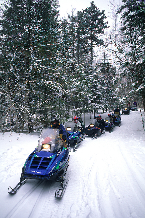 Snow mobiling adventure with riders thru the winter trails in New England USA on sno