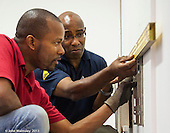Plumbing instructor and trainee plumbers fitting a radiator, Able Skills training centre, Dartford, Kent.