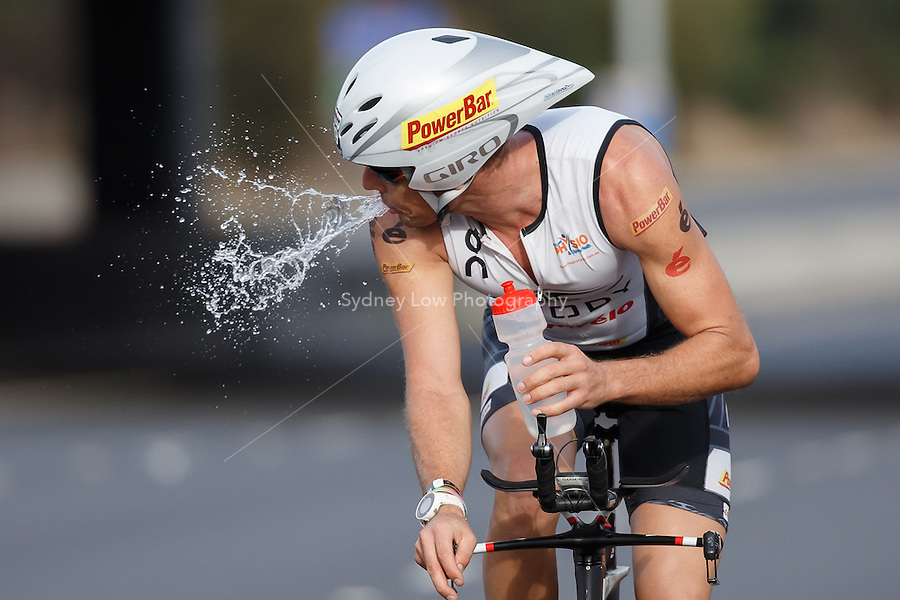 ADAM GORDON (NZL) spits out his drink at the turn around of the bike leg at the IRONMAN Asia-Pacific Championship in Melbourne, Australia on Sunday March 23, 2014. (Photo Sydney Low / sydlow.com)