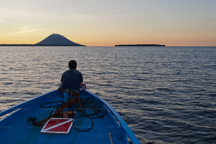 The resting volanco Manado Tua looms above Bunaken Island (on the left) and Siladen Island (right side) at sunset.  Viewed at sunset from the boat to Siladen Island, Bunaken, off North Sulawesi, Indonesia.