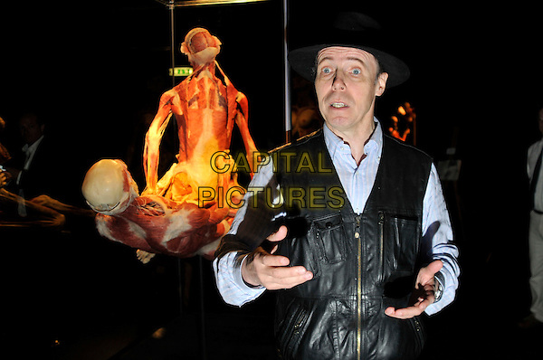 DR. GUNTHER VON HAGENS & THE SUSPENDED ACT.Press conference for the new sex plastinates which is part of the Body Worlds & the Mirror of Time exhibition at the O2 Arena, Greenwich, south-east London, England..June 23rd, 2009.bodyworks body works half length muscles internal organs flesh muscle skin models bone sexual position half length black hat blue shirt waistcoat hands .CAP/PL.Phil Loftus/Capital Pictures.