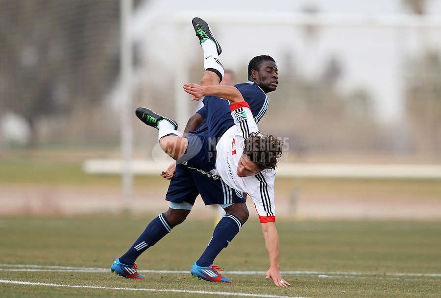 Jan. 25, 2013; Casa Grande, AZ, USA: New England Revolution midfielder Ryan Guy (white) is upended by Sporting KC midfielder Peterson Joseph as he goes for a header during a preseason game at Grande Sports World. Mandatory Credit: Mark J. Rebilas-USA TODAY Sports