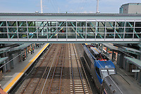 Amtrak Regional Rail Movement captured at the Commuter Train Station under construction in Fairfield CT. Engine passing under the newly constructed pedestrian walkway connecting east and westbound platforms as seen right and left in photo.