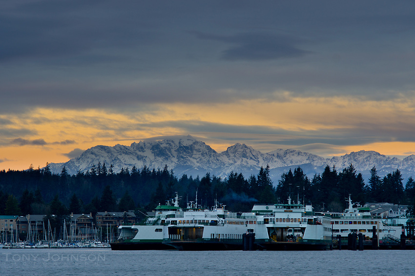 The Olympic Mountains stand above the ships and pleasure craft in Bainbridge Island's Eagle Harbor