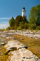 Foliage surrounding the Cana Island Lighthouse tower is decked out in spring foliage color, Cana Island, Door County, Wisconsin
