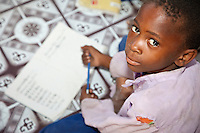 Jambiani, Zanzibar, Tanzania.  Muslim African Schoolboy with his Copybook.  The Indian Ocean beach is less than a hundred feet from this boy's classroom, explaining why his face is speckled with grains of sand.