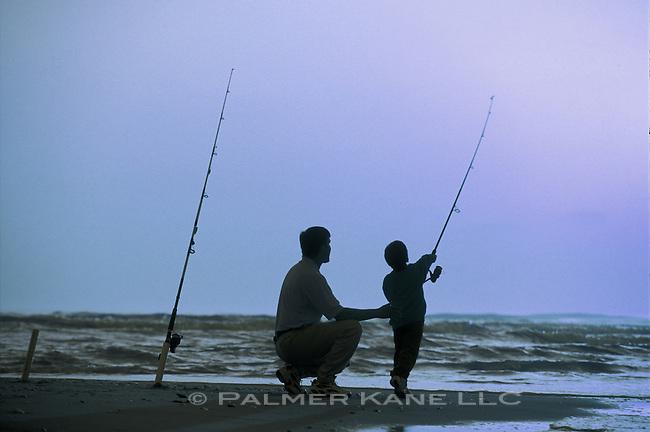 Father and son surf fish at twilight on Carolina's Cape Fear, Bald Head Island, N. Carolina, USA