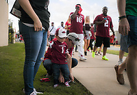 NWA Democrat-Gazette/CHARLIE KAIJO Taylor Shouse of Conway ties the shoes of Sawyer Shouse, 2, before a football game, Saturday, October 6, 2018 at Donald W. Reynolds Razorback Stadium in Fayetteville.