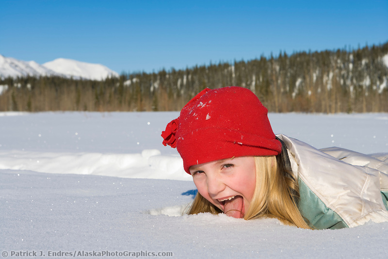 Julia hicker plays in the snow in Wiseman, Brooks Range, Alaska