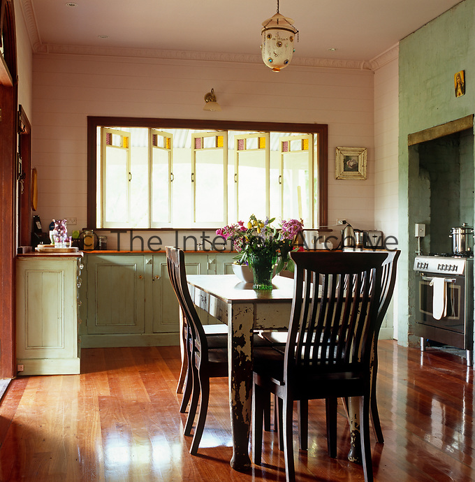 The kitchen with pale green painted cupboards has a simple table and rustic chairs in the centre of the room