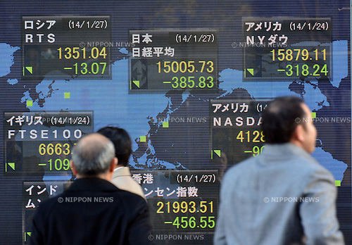 January 27, 2014, Tokyo, Japan - Pedestrians examine stock quotes on the electric bulletin board of a Tokyo brokerage on Monday, January 27, 2014. Tokyo stocks traded sharply lower with the Nikkei Stock Average briefly falling below the 15,000 mark for the first time in about two months. The Nikkei index closed at 1,5005.73, down 385.83 points from Friday.  (Photo by Natsuki Sakai/AFLO)
