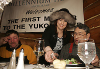 Brooke McGrath of the Millenium hotel serves Paul Gebhart a portion of his 7-course meal  in Ruby for being the first musher to the Yukon River.  Paul's dining guest is 1975 Iditarod champion Emmitt Peters of Ruby.