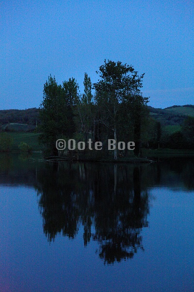 lake with island and trees in the early morning France Aude