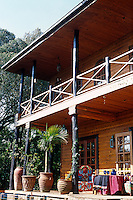 The veranda which runs along the length of the house incorporates locally felled tree trunks