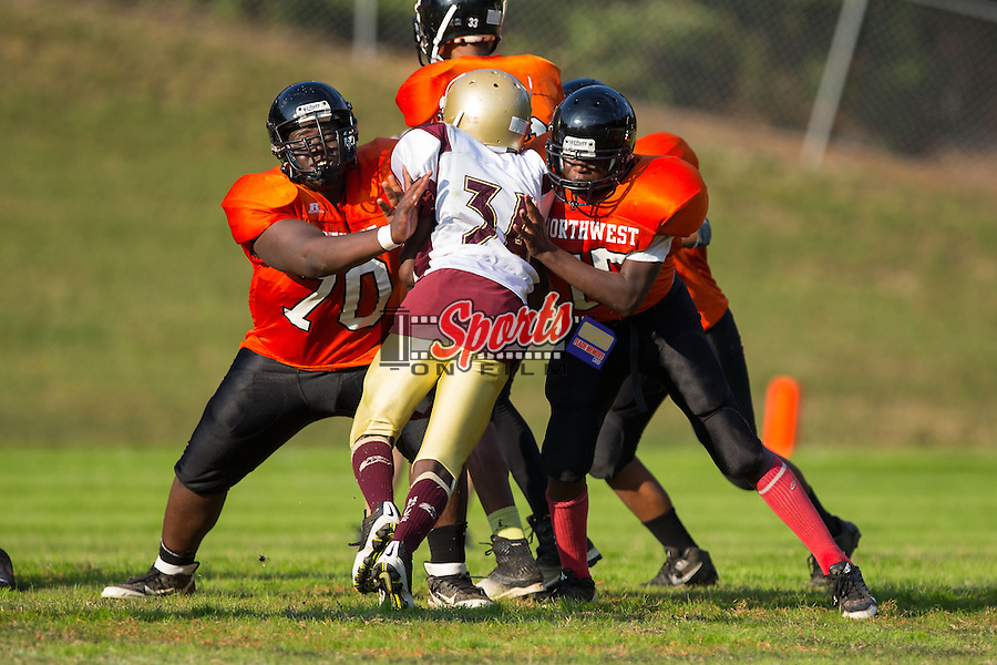 Kamryn Robinson (34) of the Winkler Wolves is blocked by Trajon Truesdale (70) and Andre Hill (75) of the Northwest Cabarrus Titans at Trojan Stadium October 1, 2014, in Concord, North Carolina.  The Wolves defeated the Titans 24-22.  (Brian Westerholt/Sports On Film)
