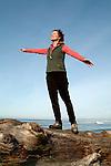 Woman balancing on log near ocean