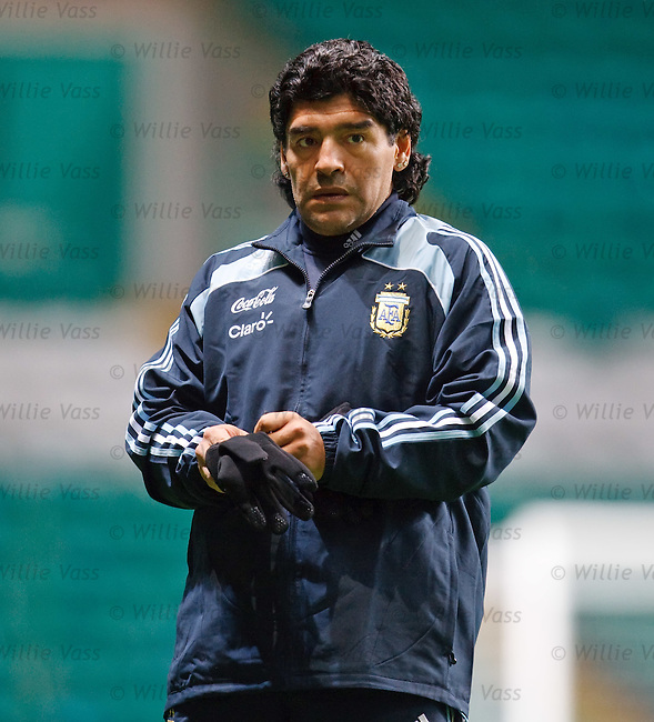 Diego Maradona pulls on some wooly gloves to ward off the chill Scottish air