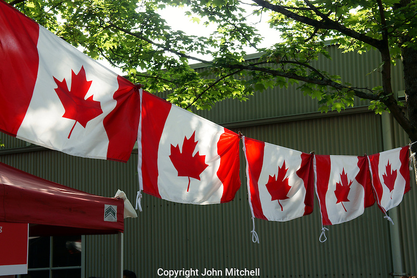 VANCOUVER, CANADA, 1st July 2013. Canadian red maple leaf flags at Canada Day celebrations on Granville Island in Vancouver, BC. Canada Day or Fete du Canada is an annual national holiday celebrating Canada's birth as a nation  in 1867.