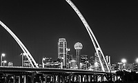 BW Dallas Skyline McDermott Bridge - The new Margaret McDermott Bridge in downtown Dallas in black and white with city skyline after dark. This is a steel bridge suspended with two arches over the Trinity River previously IH30 and is part of the Trinity project partially designed by Santiago Calatrava. This bridge is also designed to accomodate a pedestrian and bike path to join the the area other hike and bike trails. Also in this image is the Reunion Tower, the Bank of America Plaza, Renaissance Tower, Comercia Bank Tower, Omin Hotel, along with many other downtown high rise buildings. Dallas has some of the tallest buildings in Texas second only to Houston. The Bank of America Plaza stands at 921 feet and the Renaissance Tower at 886 feet as two of the tallest buildings in the southern US. Dallas is also the fourth most populous city in Texas with an estimate of 1, 197 million, but the Dallas-Fort Worth metroplex has the greatest population in Texas at over 7 million for the 2016 census. Dallas is the main draw to the area with it modern city it has become a main area for coporate head quarters like AT&T, ExxonMobile, Nokia, Rockwell, and the list goes on for fortune 500 companies. Dallas is located in north Texas and is the largest inland metropolitan area and has grown to become a industrial and finacial district in Texas.  Alo Dallas has it share of culture with it museum district with some of the finest museums like the Dallas Museum of Art, the Crow Collection of Asian Art and the Nasher Sculpture Center. Also is the Dealy six floor museum which commemorates the site of President John F Kenndys assassination in the downtown Dallas in 1963. These wall art images  could be used for hotel, office, hospitality art and for residential projects for home deocr.