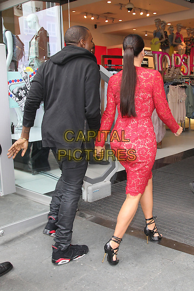 Kim Kardashian and Kanye West visit Selfridges, London, England..May 18th, 2012.full length red pink lace dress black jacket jeans denim sneakers trainers  couple holding hands back behind rear ponytail.CAP/HIL.©John Hillcoat/Capital Pictures.