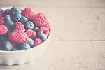 a bowl of fresh pink raspberries & ripe blueberries