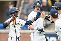 Michigan Wolverines second baseman Ako Thomas (4) is greeted by his teammates after scoring against the Maryland Terrapins on April 13, 2018 in a Big Ten NCAA baseball game at Ray Fisher Stadium in Ann Arbor, Michigan. Michigan defeated Maryland 10-4. (Andrew Woolley/Four Seam Images)