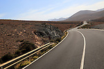 Tarmac road crossing barren desert mountainous land between Pajara and La Pared, Fuerteventura, Canary Islands, Spain