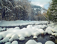 Snow-pillowed rocks in the South Fork Snoqualmie River, Snoqualmie Pass, Cascade Mountains, Washington State.