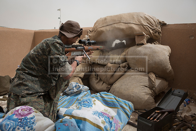 28/09/2014. Al-Yarubiyah, Syria. Using a home made 14.5mm rifle, a sniper belonging to Syrian Kurdish YPG forces in Al-Yarubiyah, Syria, fires at Islamic State positions across the border in Rabia, Iraq.<br /> <br /> Facing each other across the Iraq-Syria border, the towns of Al-Yarubiyah, Syria, and Rabia, Iraq, were taken by Islamic State insurgents in August 2014. Since then The town of Al-Yarubiyah and parts of Rabia have been re-taken by fighters from the Syrian Kurdish YPG. At present the situation in the towns is static, but with large exchanges of sniper and heavy machine gun fire as well as mortars and rocket propelled grenades, recently occasional close quarter fighting has taken place as either side tests the defences of the other.