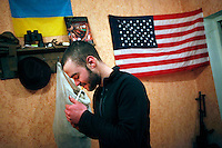 "UKRAINE, 02.2016, Novohrodivka, Oblast Donetsk. Ukrainian-Russian conflict concerning Eastern Ukraine / Foreign volunteers (""Task Force Pluto"") fighting with the far-right militia Pravyi Sektor against the Russian-backed separatists: Cowboy (USA) lights a good-morning cigarette in front of the Ukrainian and the US flag. © Timo Vogt/EST&OST"