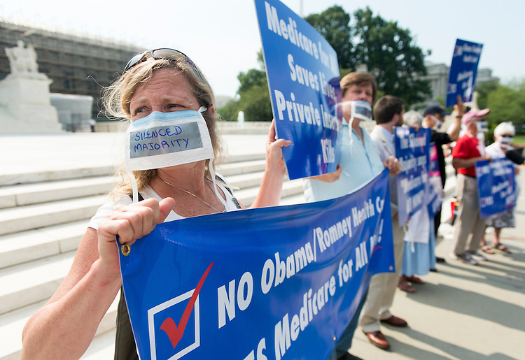 """UNITED STATES - JUNE 25: Protesters against the Affordable Care Act and calling for """"Medicare for All"""" hold signs in front of the Supreme Court as protesters and the media gathered for a possible ruling from the court on the Affordable Care Act on Monday, June 25, 2012. (Photo By Bill Clark/CQ Roll Call)"""