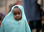 A newly arrived Somali girl waits with her family to be processed in the reception center of the Dagahaley refugee camp, part of the Dadaab refugee complex in northeastern Kenya.