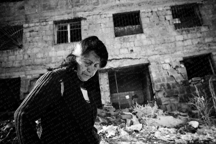 Gohar Boyadzyan walks outside her partly demolished home in Gyumri where she still lives after the 1988 earthquake. Gyumri has lost the most of its industrial capacities, cultural institutions, buildings.