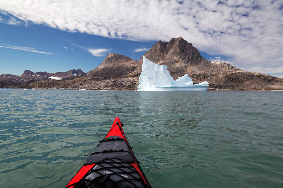Bow of sea kayak with pinnacled iceberg and mountains, Sammileq Fjord, Ammassalik Island, East Greenland