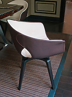 The comfortable tub chairs around the dining table are made of soft cream and aubergine coloured leather and the dark stained oak floor is covered with a leather rug