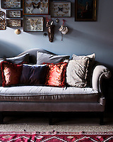 A framed butterfly collection is displayed above an elegant grey velour sofa