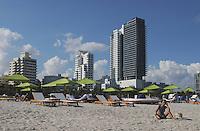 An elegant woman basking in the afternoon sun along luxurious South Beach, Miami Beach Florida.