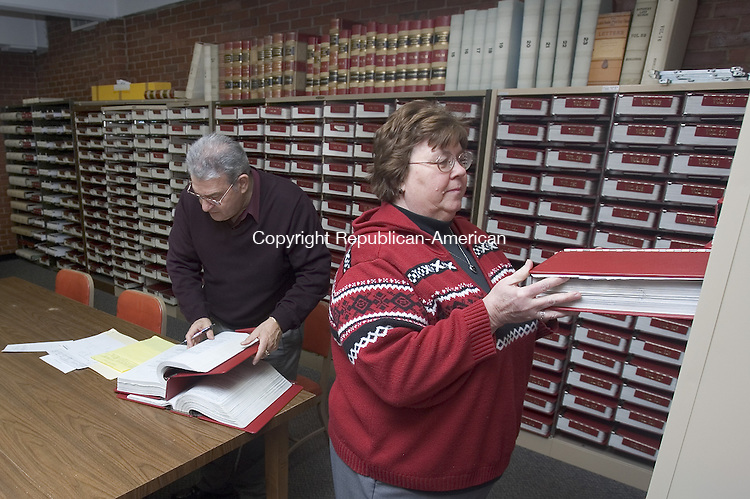 SOUTHBURY, CT. 28 January 2008-012808SV01--From left, Stephen Volman of East Haven searches for a title as Assistant Town Clerk Geraldine DeVoid returns records to the town vault in Southbury Monday. The town is looking for more space to store the records.<br /> Steven Valenti Republican-American