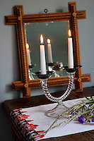 A 20th century mirror with a carved wooden frame reflects the flickering light from a Murano glass candlestick on the dining table