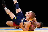 11 DEC 2011 - LONDON, GBR - Aniuar Geduev (RUS) (in red) attempts to overpower Andrew Howe (USA) (in blue) during the men's  74kg category final at the London International Wrestling Invitational and 2012 Olympic Games test event at the ExCel Exhibition Centre in London, Great Britain (PHOTO (C) NIGEL FARROW)