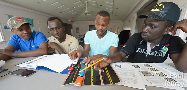 Martin Mayiani, second from right, teaches a class on driving at a Presbyterian church in Harrisonburg, Virginia. Mayiani is a former refugee who came to the U.S. four years ago. He volunteers to teach these newly arrived Congolese refugees how to pass the state's driving test, which isn't available in Swahili. They use toy cars to understand the nuances of how to drive in the U.S. <br /> <br /> Mayiani and his students were resettled in the Harrisonburg area by Church World Service.<br /> <br /> Photo by Paul Jeffrey for Church World Service.