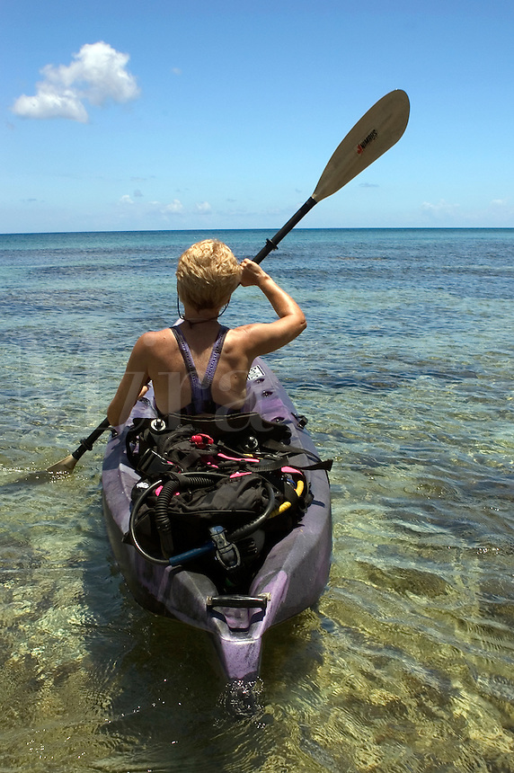 Woman (MR) with scuba equipment paddling a kayak in Cayman Brac, Cayman Island