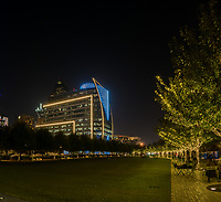 A vertical pano view of the Klyde Warren Park after dark as the trees create a path through the darkness in downtown Dallas.  In the background you can see the very colorful Hunt Oil building as the colorful blue light that signal another win by the Dallas Cowboys.