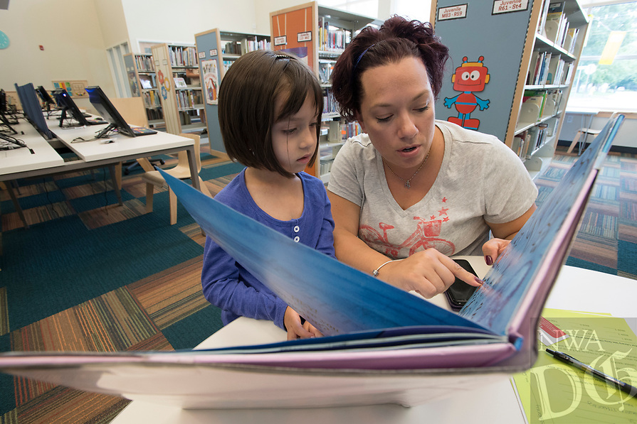 NWA Democrat-Gazette/J.T. WAMPLER Heather McHaney, of Siloam Springs, reads to her daughter Channa McHaney, 4, Wednesday July 5, 2017 at the Siloam Springs Public Library. Saturday July 8th is the last day to sign up for the Summer Reading Incentiver Program for children ages 3-18. For more information about activities at the library call 479-524-4236.
